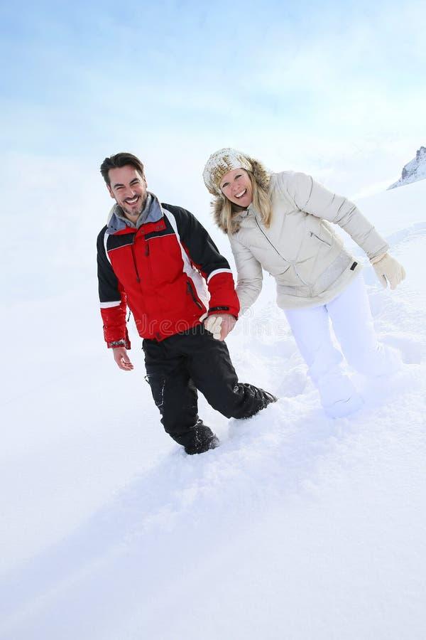 Couples marchant dans la neige image stock