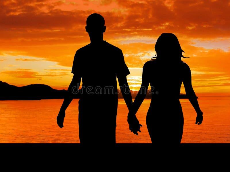 Couples marchant dans le coucher du soleil photo stock