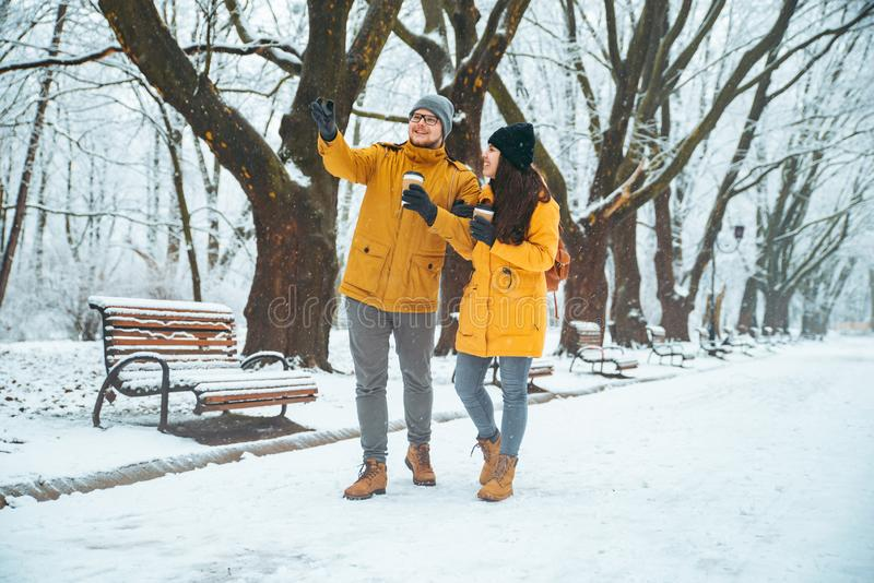 Couples marchant par le café potable neigé de parc de ville pour aller diriger quelque chose directement photographie stock libre de droits