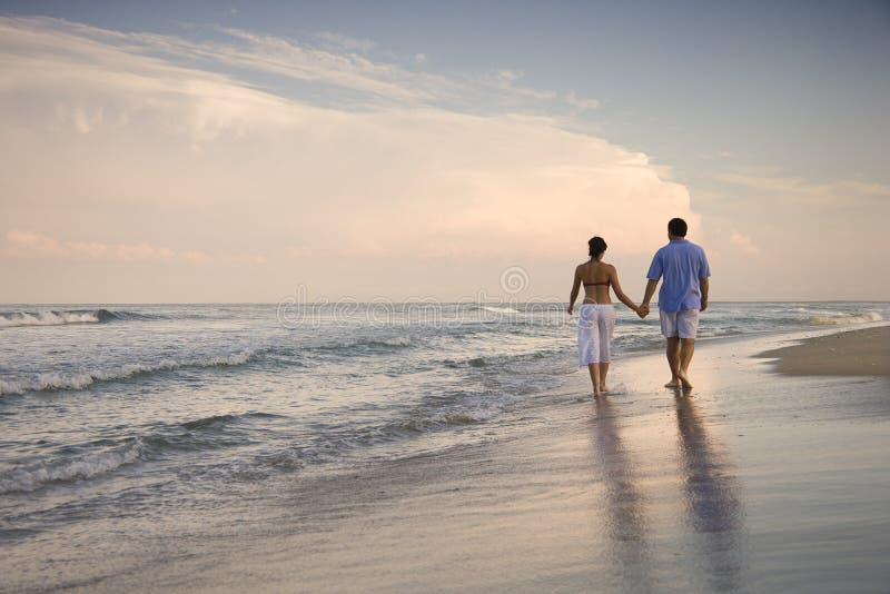 Couples marchant sur la plage images stock