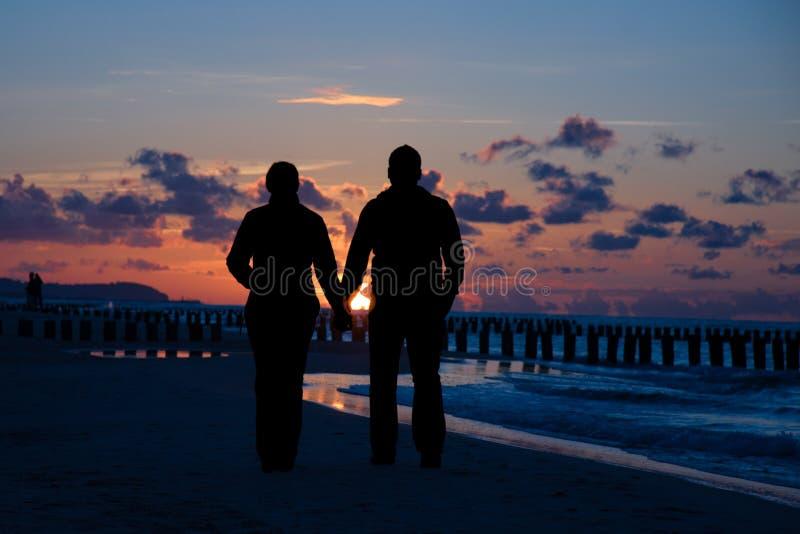 Couples marchant sur la plage images libres de droits