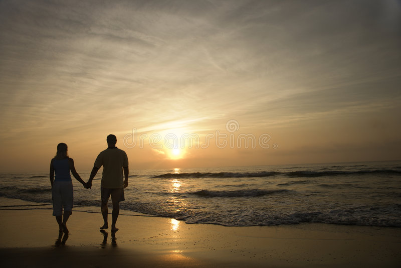 Couples marchant sur la plage photo stock