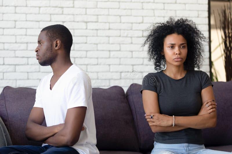 Couples mariés mécontents se reposant séparément sur le divan et ne parlant pas image stock