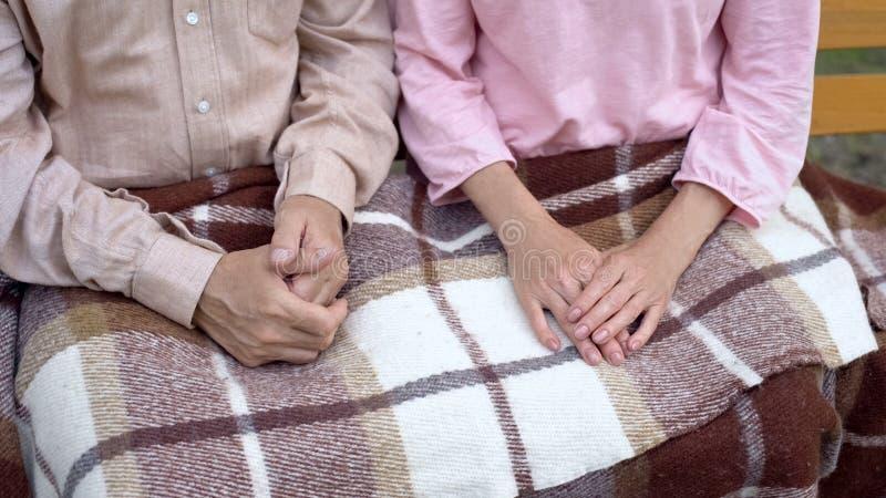 Couples mariés mûrs se reposant sur le banc de parc couvert de couverture, maison de repos photographie stock libre de droits