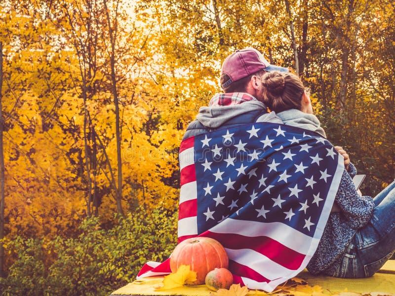 Couples mari?s heureux tenant le drapeau des USA photo stock