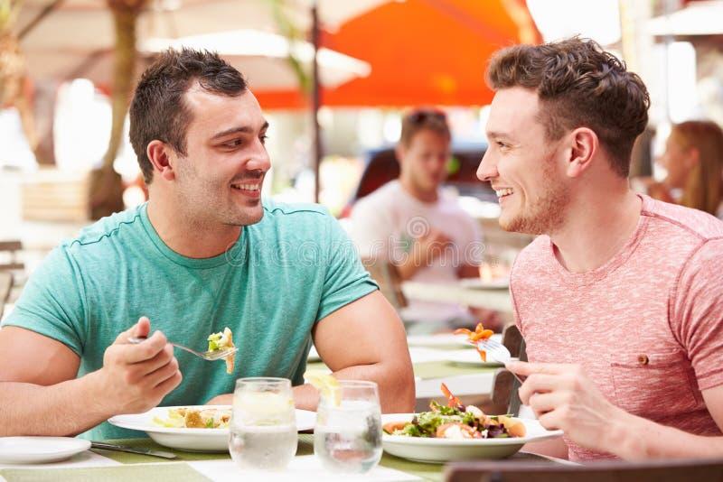 Couples masculins appréciant le déjeuner dans le restaurant extérieur image libre de droits