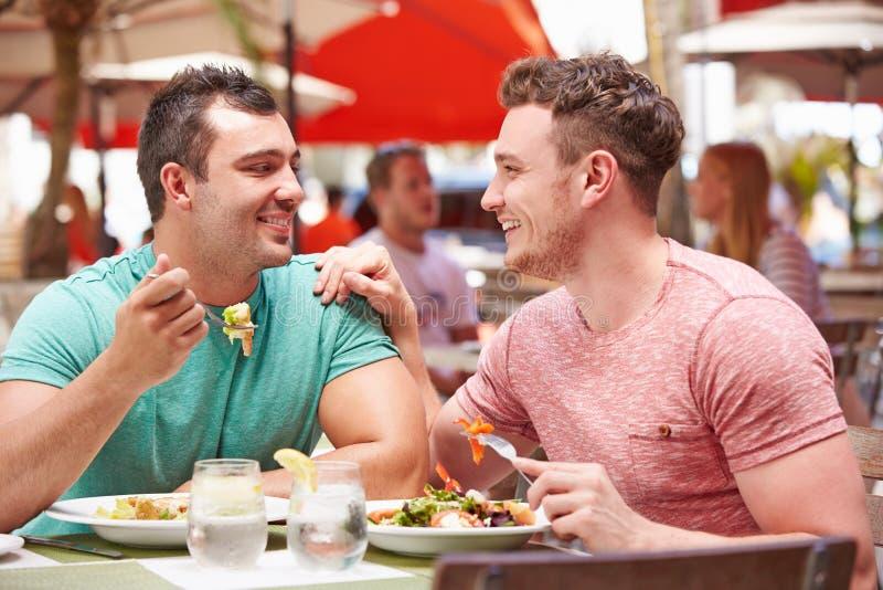 Couples masculins appréciant le déjeuner dans le restaurant extérieur photo libre de droits