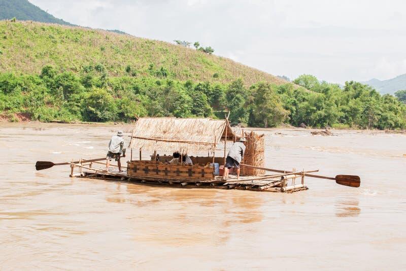 Couples masculins transportant la maison par radeau en bambou de radeau sur la rivière de Kok, rive tropicale de Mountain View La photographie stock libre de droits
