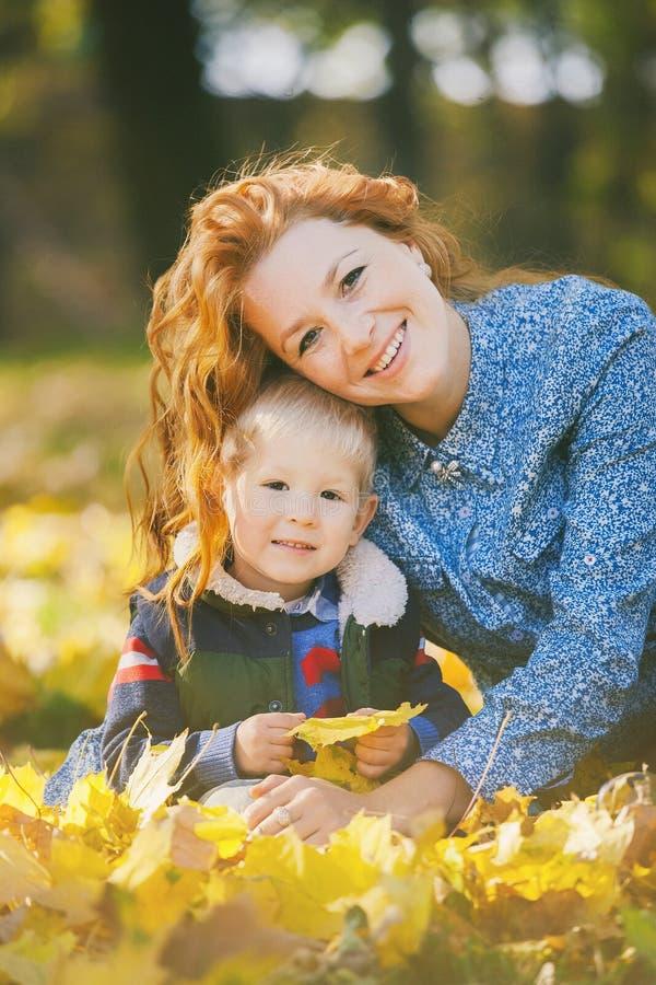 Couples mignons de la maman et du fils posant et étreignant en parc d'automne images libres de droits