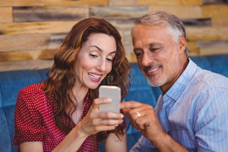 Download Couples Mignons Regardant Leurs Téléphones Photo stock - Image du attrayant, caucasien: 56486318
