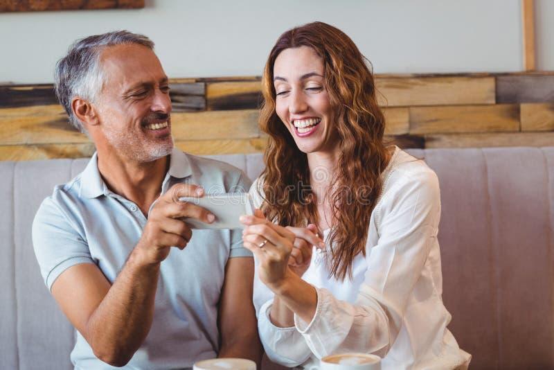 Download Couples Mignons Regardant Leurs Téléphones Photo stock - Image du people, café: 56486488