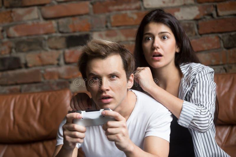 Couples millénaires inquiétés jouant le jeu vidéo d'ordinateur image stock