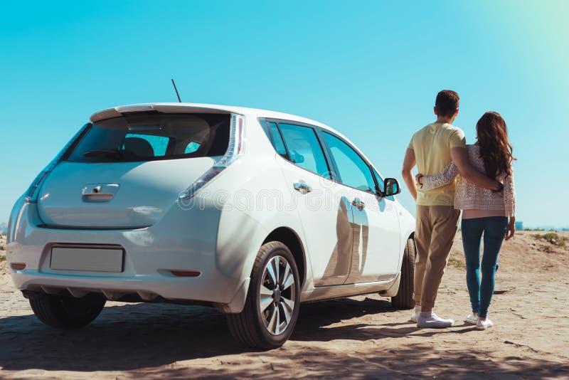 Couples modernes mignons laissant leur voiture et se dirigeant à la plage photographie stock