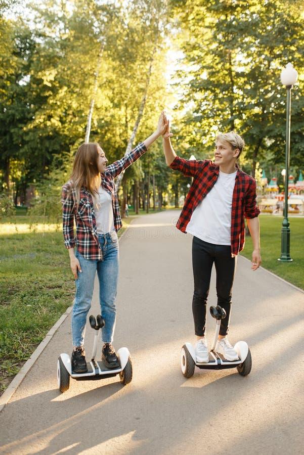 Couples montant sur le panneau de compas gyroscopique en parc, transport d'eco image libre de droits