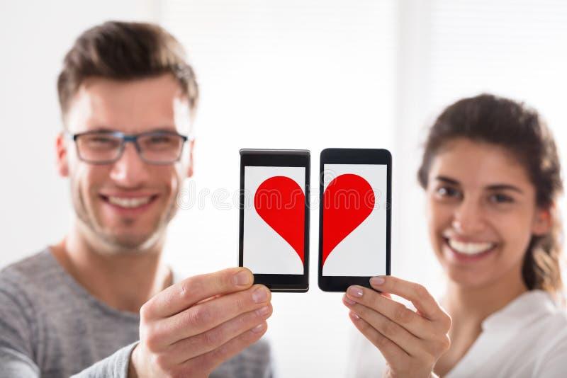 Couples montrant la forme de coeur au téléphone portable images libres de droits