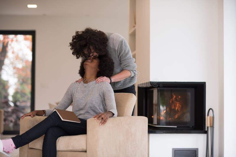 Couples multi-ethniques étreignant devant la cheminée photos stock