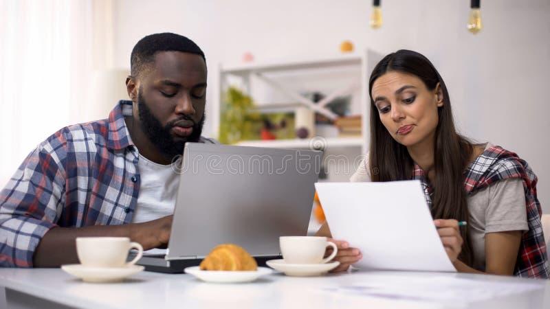 Couples multi-ethniques des indépendants travaillant ensemble à la maison utilisant l'ordinateur, le travail photos stock