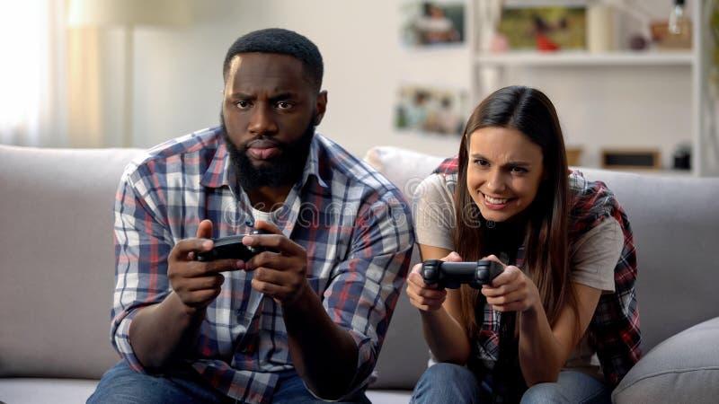 Couples multi-ethniques gentils ayant l'amusement, jouant le jeu vidéo à la maison, temps libre photographie stock