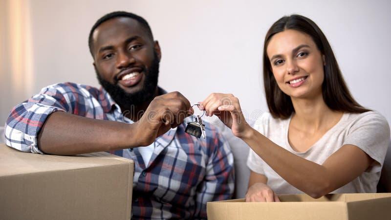 Couples multi-ethniques heureux tenant les boîtes de carton et la chaîne principale de maison, relocalisation images stock