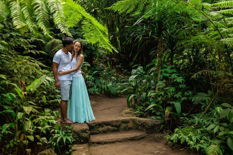 Couples multiraciaux de baiser heureux étreignant sur la traînée de marche dans de jeunes couples de métis de forêt tropicale des photo stock