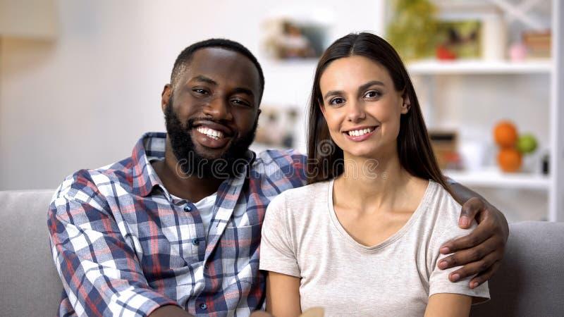 Couples multiraciaux de sourire étreignant et regardant à la caméra, sécurité sociale images stock
