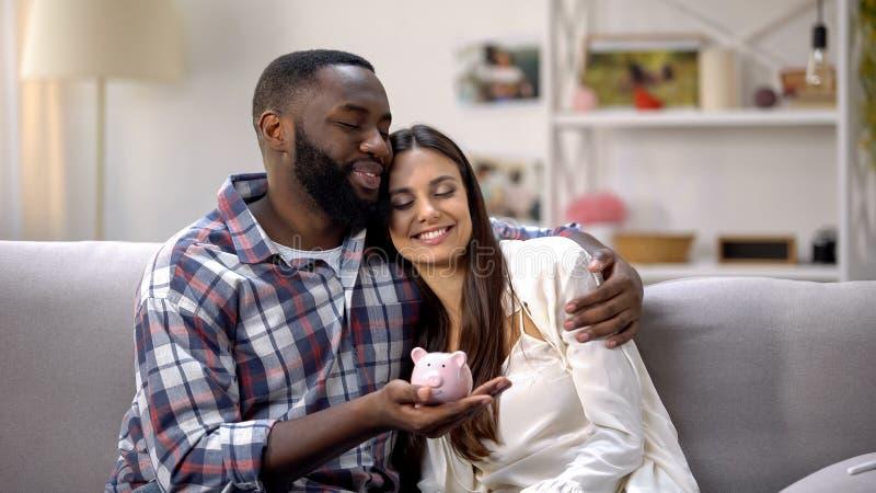 Couples multiraciaux tenant la tirelire et étreignant, hypothèque pour de jeunes familles photographie stock libre de droits