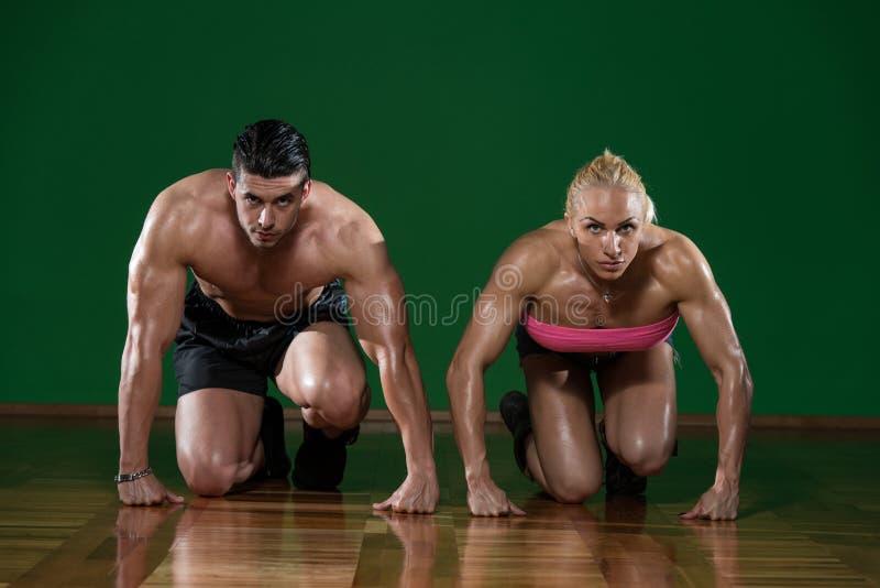Couples musculaires forts se mettant à genoux sur le plancher photos libres de droits