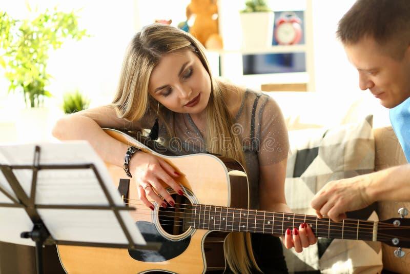 Couples musicaux d'atelier ? la maison jouant la guitare image libre de droits