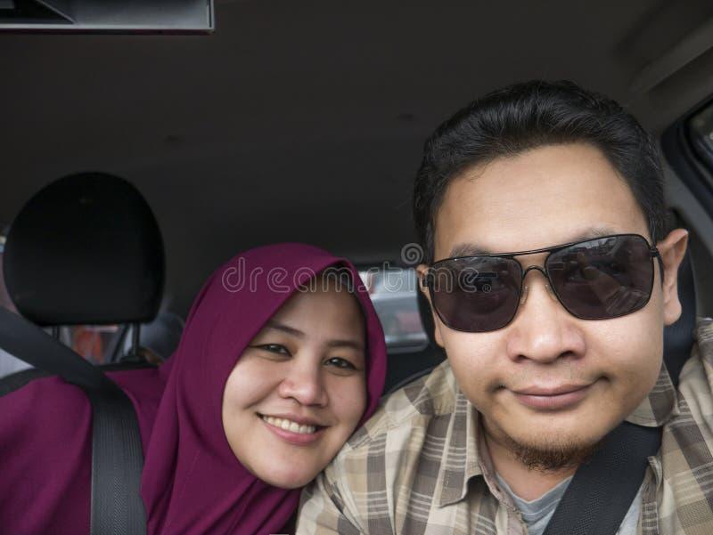 Couples musulmans asiatiques drôles prenant Selfie dans la voiture images libres de droits