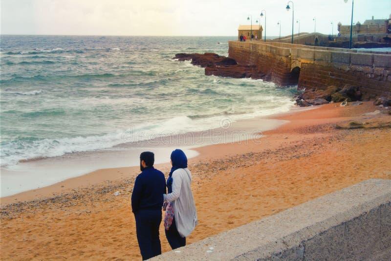 Couples musulmans de famille sur la plage d'hiver photographie stock