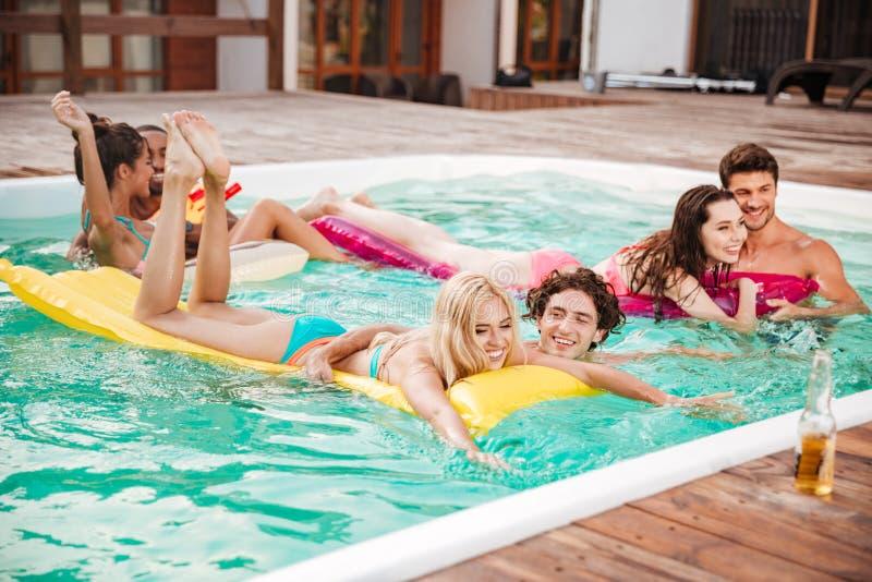 Couples nageant dans la piscine et ayant l'amusement photographie stock libre de droits
