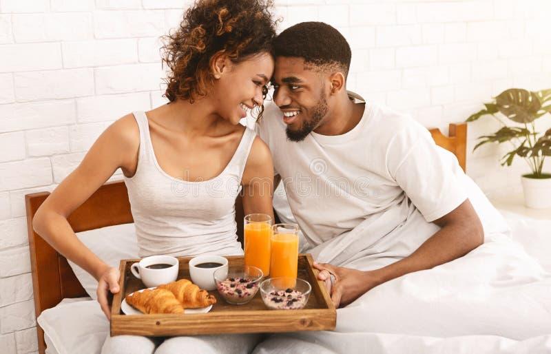 Couples noirs heureux appréciant le petit déjeuner dans le lit photo libre de droits