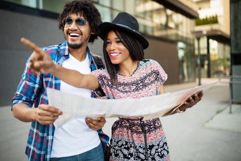 Couples noirs heureux sur la ville guidée de vacances avec la carte photos libres de droits