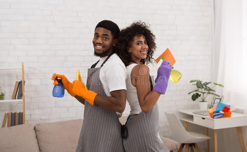 Couples noirs heureux tenant des détergents pendant le nettoyage à la maison image libre de droits