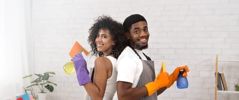 Couples noirs heureux tenant des détergents pendant le nettoyage à la maison image stock