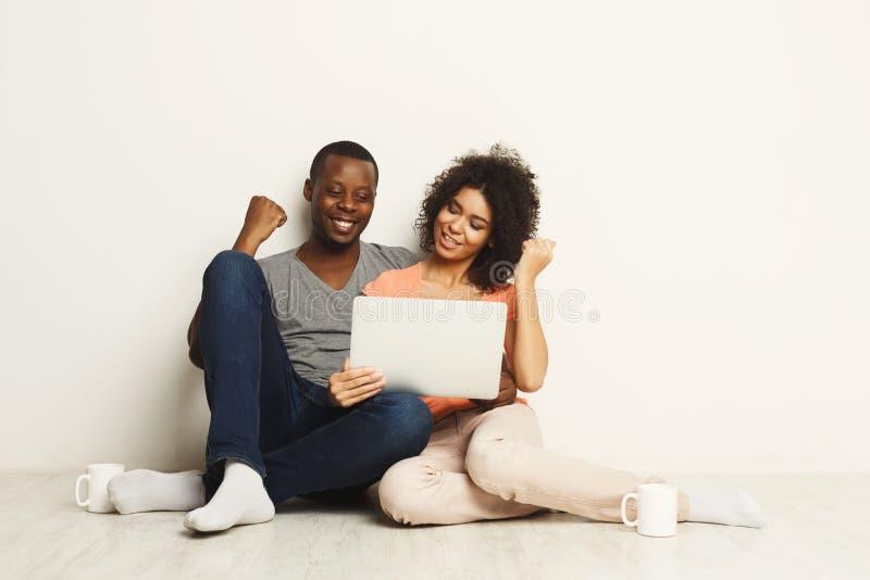 Couples noirs réussis gagnant en jeu sur Internet image stock