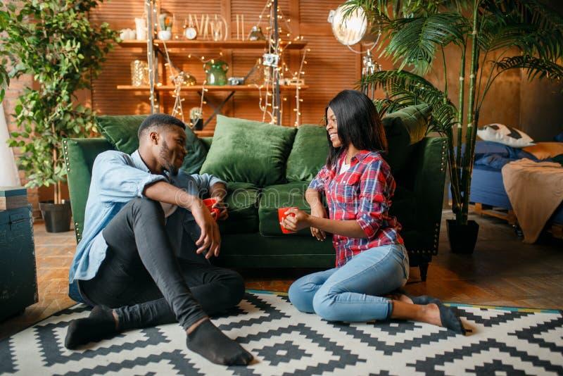 Couples noirs se reposant sur le plancher et le caf? de boissons images stock
