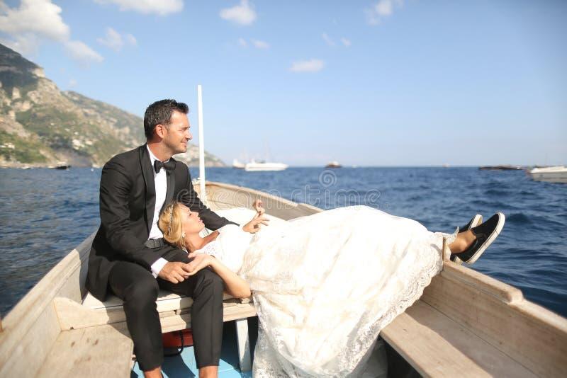 Couples nuptiales se reposant dans un bateau en bois photo libre de droits