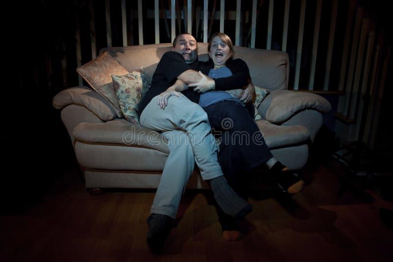 Couples observant le film effrayant à la TV images stock