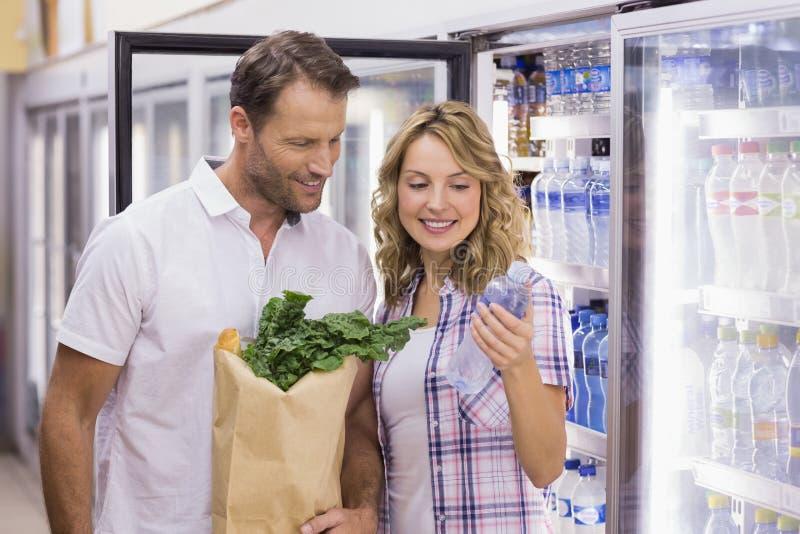Download Couples Occasionnels De Sourire Regardant La Bouteille D'eau Photo stock - Image du réfrigérateur, nourriture: 56488142
