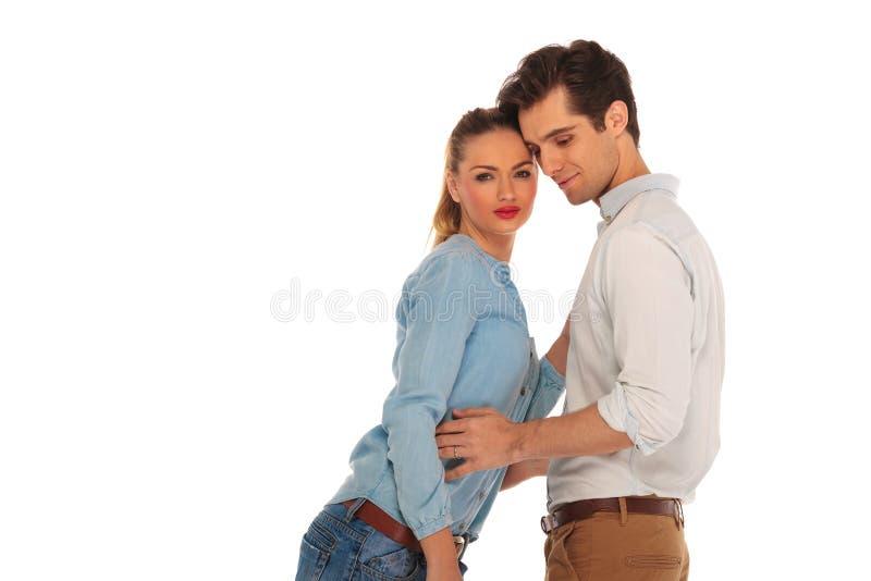 Couples occasionnels posant à l'arrière-plan de studio photo libre de droits