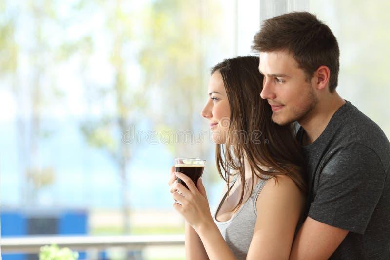 Couples ou mariage regardant par une fenêtre images stock