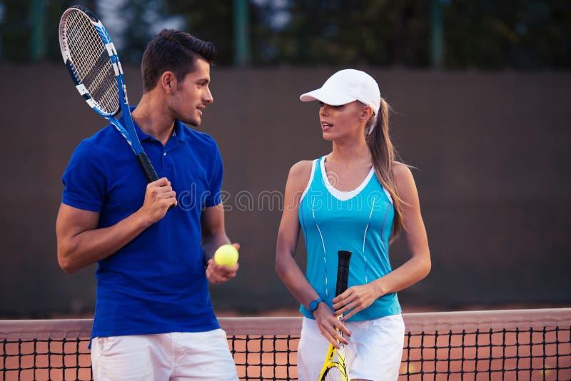 Couples parlant au court de tennis image stock
