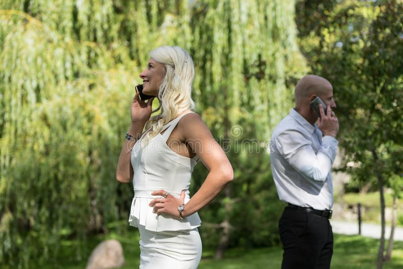 Couples parlant au téléphone mobile ou intelligent L'homme et la femme parlent avec le téléphone Les jeunes utilisent le téléphon photos stock