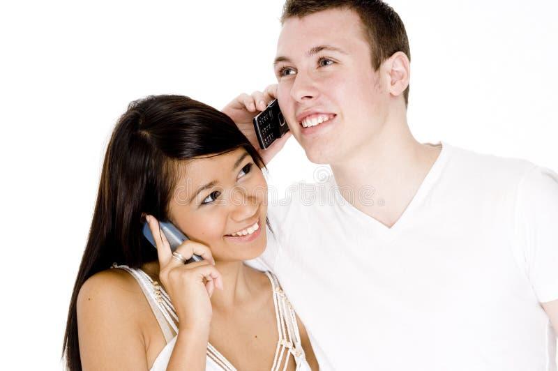 Couples parlant aux téléphones photos stock
