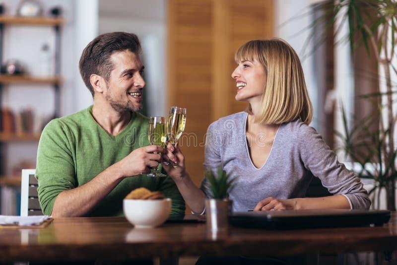 Couples parlant pendant la nuit dans le salon à la maison et boire du vin image stock
