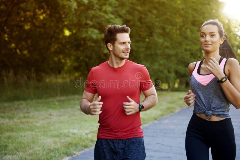 Couples parlant pendant le fonctionnement de matin photographie stock libre de droits