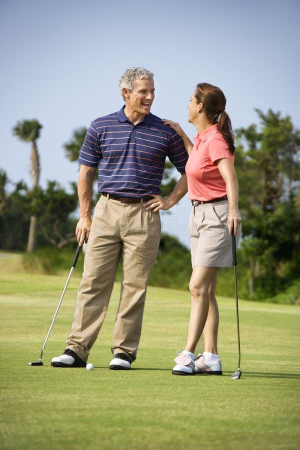 Couples parlant sur le terrain de golf image stock