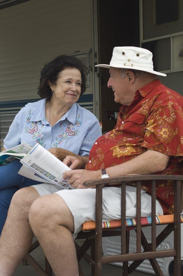Couples parlant tout en se reposant sur la chaise photo stock