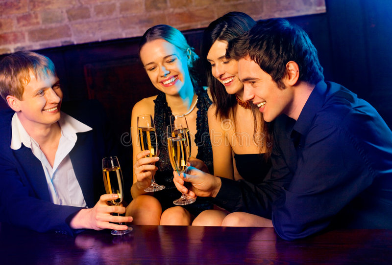 Couples at party. Two young happy smiling couples with champagne glasses at celebration, party or romantic date in night club